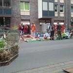 Bespflanzter Einkaufswagen und Sitzgelegenheiten auf dem Parkstreifen